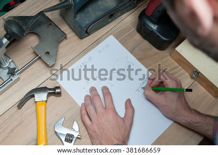 Designer with a pen and piece of paper working on a sketch for some furniture in workshop - stock photo