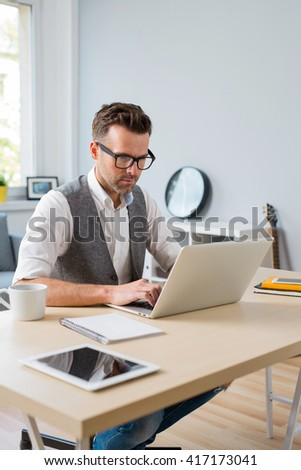 Designer working on laptop from home.