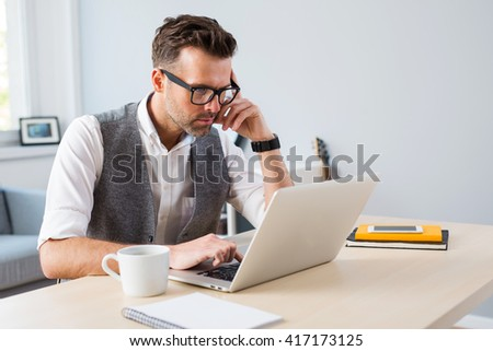 Designer working on laptop from home - freelance concept - stock photo