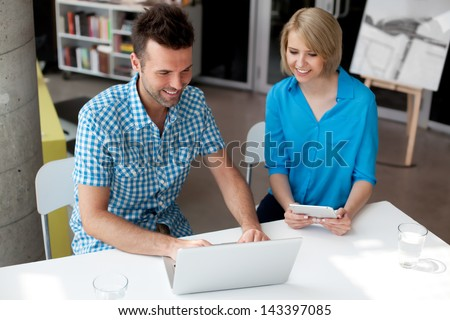 Designers working on laptop and digital tablet in the office - stock photo