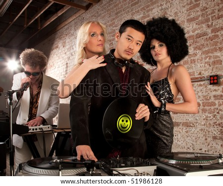 Desirable young DJ with two female admirers - stock photo