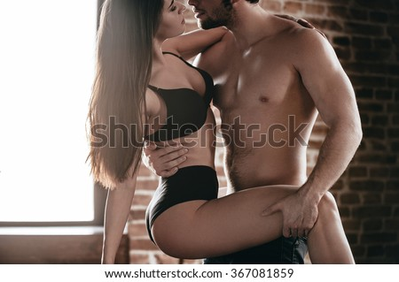 Desire and temptation. Close-up part of handsome young shirtless man carrying his girlfriend and kissing her while standing against brick wall - stock photo
