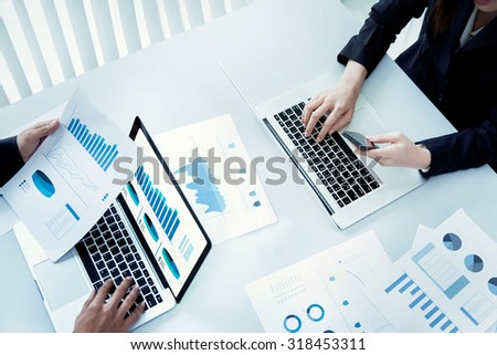 Desk businessman is using his laptop and documents as graphs. top view - stock photo