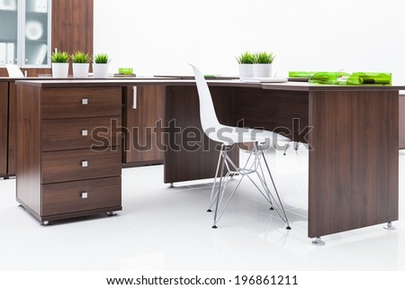 desk, chair and bookcase on a white wall - stock photo