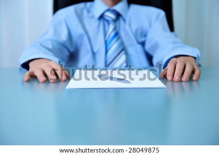 Desk detail with blank paper a pen and businessman hands - stock photo