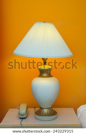 desk lamp and telephone at a hotel room - stock photo