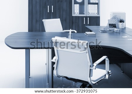 desk, leather armchair and bookcase on a white wall - stock photo