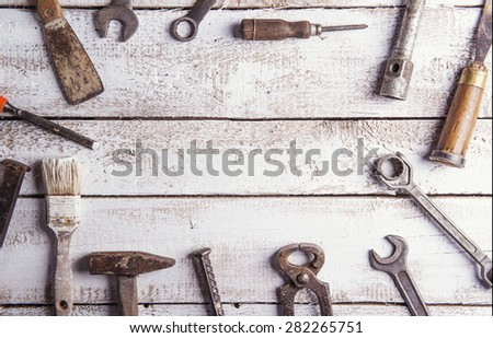 Desk of a carpenter with various tools. Studio shot on a wooden background. - stock photo