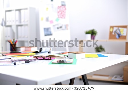 Desk of an artist with lots of stationery objects. Studio shot on wooden background - stock photo