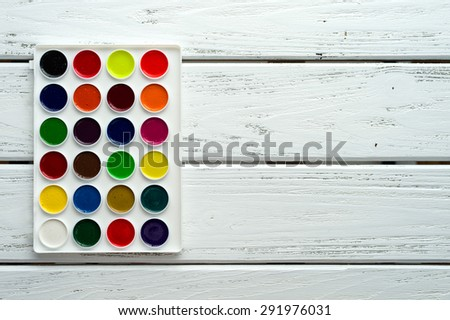 Desk of creative worker. Paints on wooden white background, top view, with copy space. - stock photo