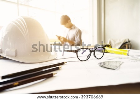 Desk of Engineering project in construction site or office with mining light.Construction concept.Engineering tools.Vintage tone retro filter effect,soft focus(selective focus)  - stock photo