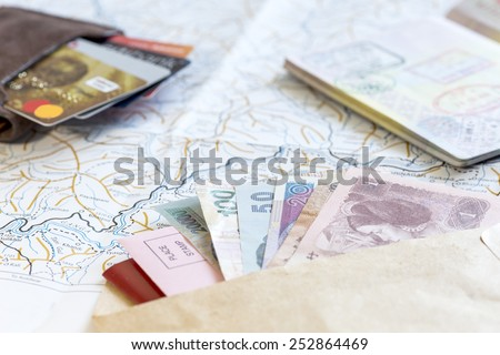 Desk of frequent traveler - angle view. The composition of essential items for trip: passport with multiple entry stamps, foreign cash notes, wallet with credit cards, and map on the background - stock photo