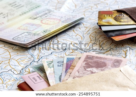 Desk of frequent traveler - angle view. The composition of essential items for trip: passport with entry stamps, cash notes of different countries, wallet with credit cards, and detailed map - stock photo