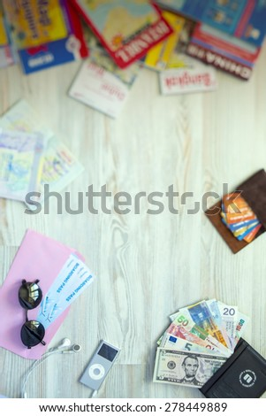 Desk of mature voyager. Travel background with essential tourist items on wooden desk passport international with entry stamps and visas exotic currency credit card many maps sunglasses from above - stock photo