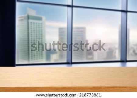 desk of wood and window with landscape of city  - stock photo
