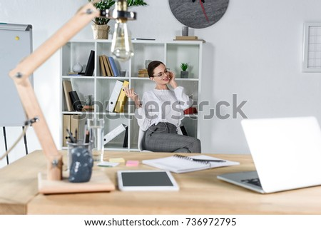 Desk with laptop and stationery in office and young businesswoman talking on phone in the background