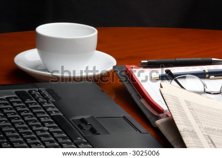 Desk with laptop, ring binder, newspaper, glasses and a cup of coffee - stock photo