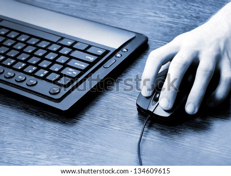 Desk with man hand on mouse - stock photo