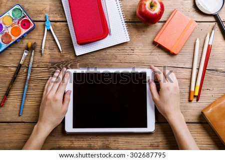 Desk with school supplies. Studio shot on wooden background.  - stock photo