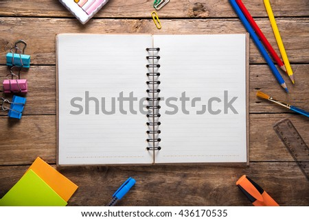 Desk with stationary and with blank notebook on wooden background. back to school concept - stock photo