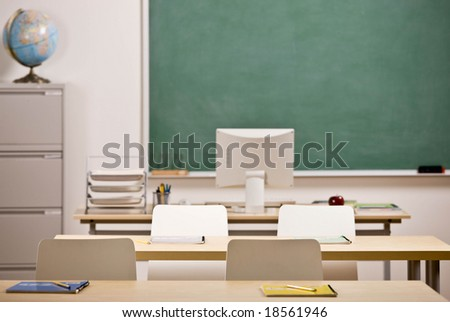 Desks, chairs, blackboard and computer in empty school classroom - stock photo