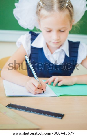 Desktop background of schoolgirl sitting at a desk, holding a pen and ready to writing in a notebook for classwork. On table there is copybook, ruler, and copy space for text. Selective focus
