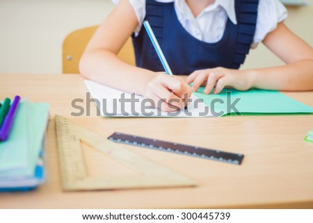 Desktop background of student sitting at a desk, holding a pen and ready to writing in a notebook for classwork or homework. On table there is a book, a copybook, a ruler, and copy space for text - stock photo