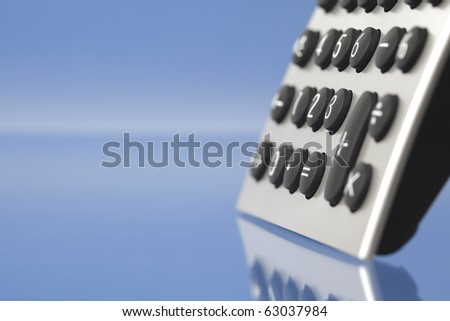 Desktop calculator, closeup on blue background - stock photo