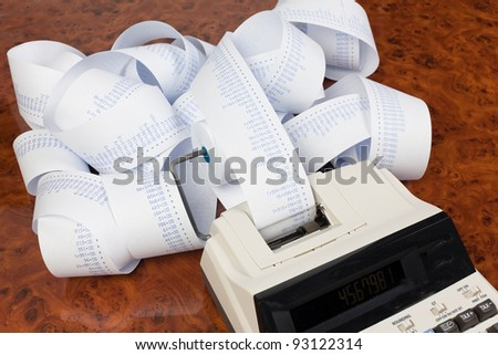 desktop calculator with calculating strip. symbol for costs, expenses, revenues and profits. - stock photo