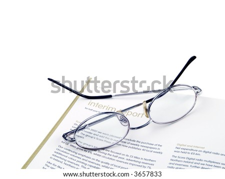 Desktop composition with annual report & glasses isolated on white