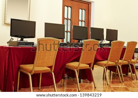 Desktop computers on table in auditorium