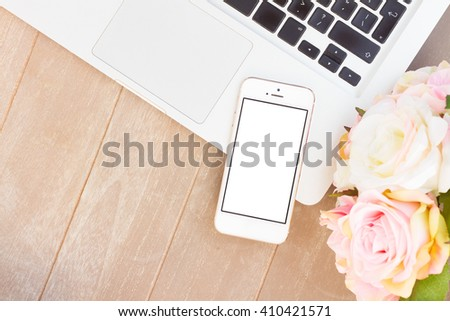 desktop scene with modern phone, laptop keyboard and flowers, copy space on blank sreen - stock photo