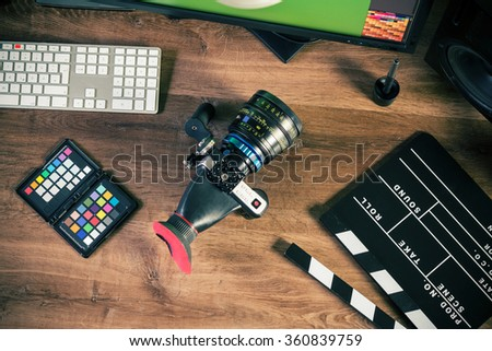 Desktop shot of a modern digital Cinema Camera and clapboard on stylish wooden desktop workplace / Background - flat lay shot