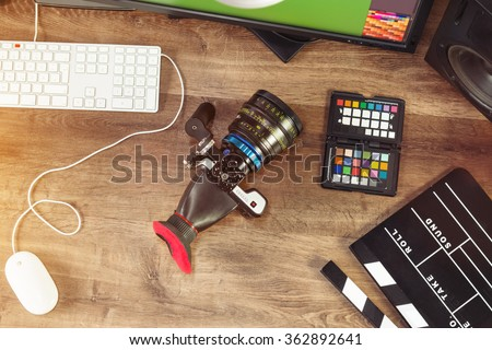 Desktop shot of a modern digital Cinema Camera and clapboard on stylish wooden desktop workplace / Background