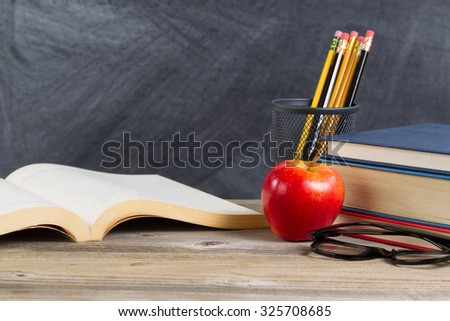 Desktop with books, red apple, reading glasses, and pencils in front of blackboard. Layout in horizontal format with plenty of copy space.  - stock photo