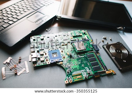 Desktop with broken disassembled laptop (computer). Electronic parts of pc: motherboard, display (monitor), hdd - stock photo