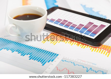 Desktop with lots of paperwork, tablet PC and a cup of fresh coffee. Business concept
