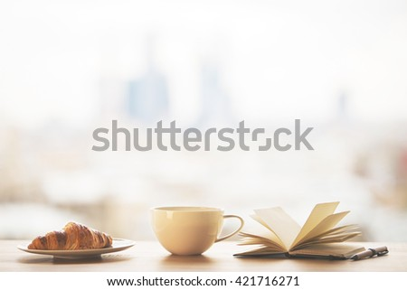 Desktop with round coffee mug, croissant on plate and open book on blurry city background - stock photo