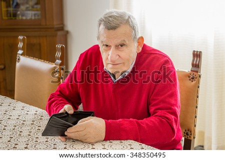 desolate and grim old octogenarian sitting at the kitchen table shows an empty wallet