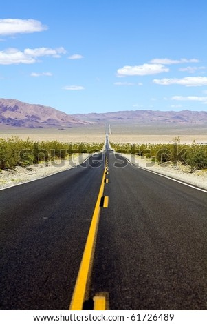 Desolate highway into Death Valley National Park - stock photo