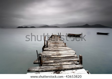 desolate pier and boat - stock photo