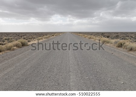 Desolation Road Dirt road leading to distant horizon under stormy skies with dust approaching from the horizon Eastern Oregon Great Basin area