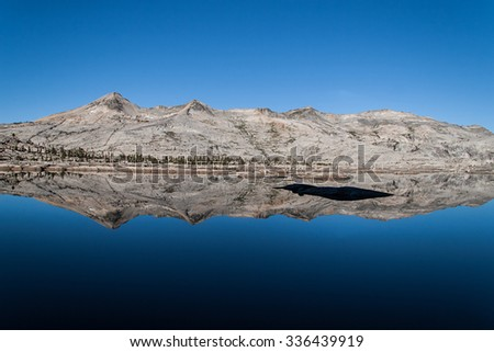Desolation Wilderness.  The Crystal Range of the Sierra Nevada mountains reflected in Lake Aloha - stock photo
