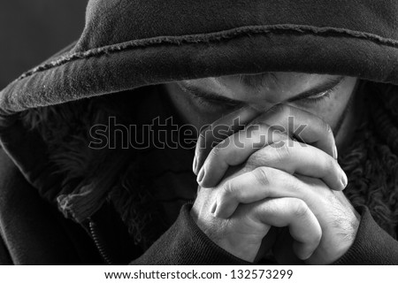 Despair bandit praying God for forgiveness - stock photo