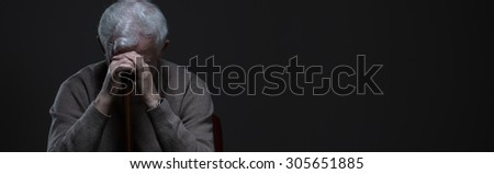 Despair elder man holding walking stick - panorama - stock photo