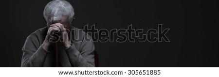 Despair elder man holding walking stick - panorama - stock photo
