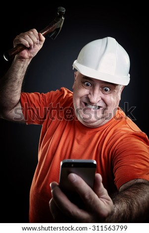 Despair repairman, hammering a smart-phone. Worker with helmet and hammer breaks smart-phone. Problem solving. - stock photo