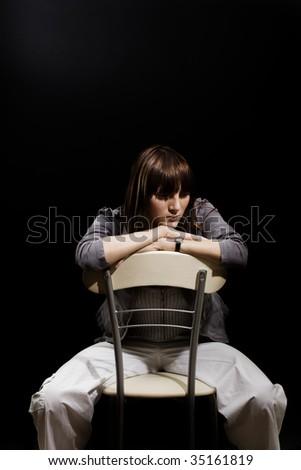 Despair - sad girl sitting on the chair in black room - stock photo