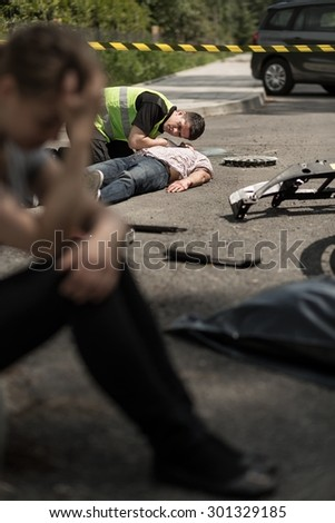 Despair young driver at road accident scene - stock photo