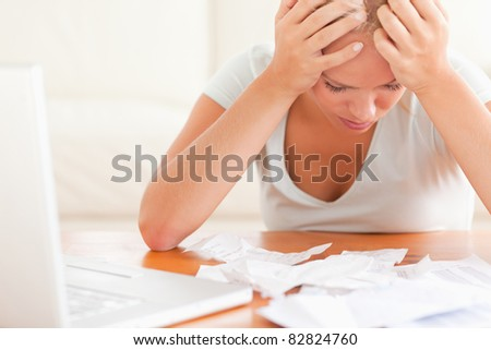 Despaired blond woman accounting in the living room - stock photo